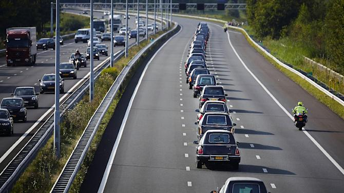 A convoy of hearses bearing the remains of passengers and crew killed in the downing of Malaysia Airlines Flight 17 makes its way along a highway near Boxtel, Netherlands, Thursday, July 24, 2014. The second flight of two military aircraft carrying remains of victims arrived in the Netherlands on Thursday. The bodies are to be taken to a military barracks in Hilversum, where a team of 25 forensic experts and dozens of support staff began working to identify remains Wednesday evening after coffins of the first flight arrived. (AP Photo/Phil Nijhuis)