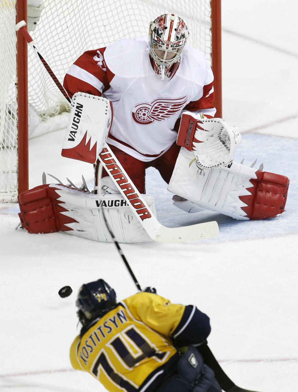 Detroit Red Wings goalie Jimmy Howard, top, blocks a shot by Nashville Predators left wing Sergei Kostitsyn (74), of Belarus, in the second period of Game 5 of a first-round NHL hockey playoff series on Friday, April 20, 2012, in Nashville, Tenn. (AP Photo/Mark Humphrey)
