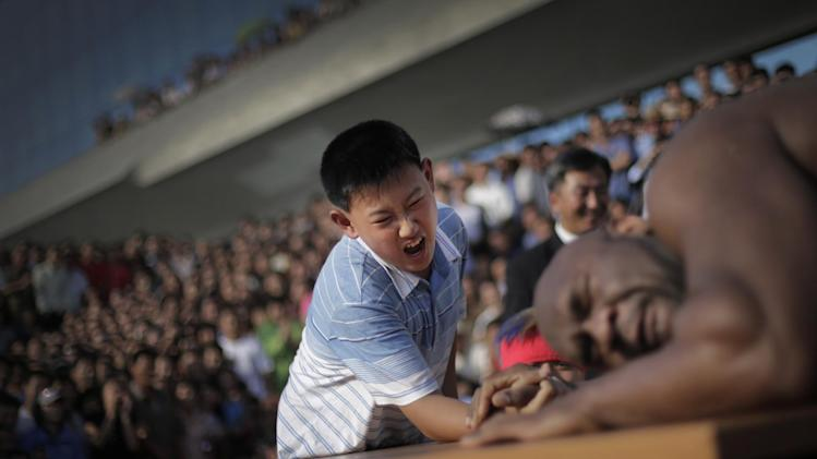 """A North Korean boy arm wrestles with former NFL player Bob """"The Beast"""" Sapp Friday, Aug. 29, 2014 in Pyongyang, North Korea. Former NFL player Sapp and a group of brawny pro wrestlers led by a Japanese politician took their oddball attempt at sports diplomacy to the streets of Pyongyang on Friday, staging a tug-war and arm wrestling competition with local children before a large and somewhat bewildered crowd of spectators. (AP Photo/Wong Maye-E)"""