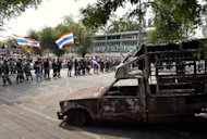 A vehicle burnt during earlier clashes lies in the foreground as anti-government protestors wave Thai flags during a stand-off with police in Bangkok, on February 18, 2014