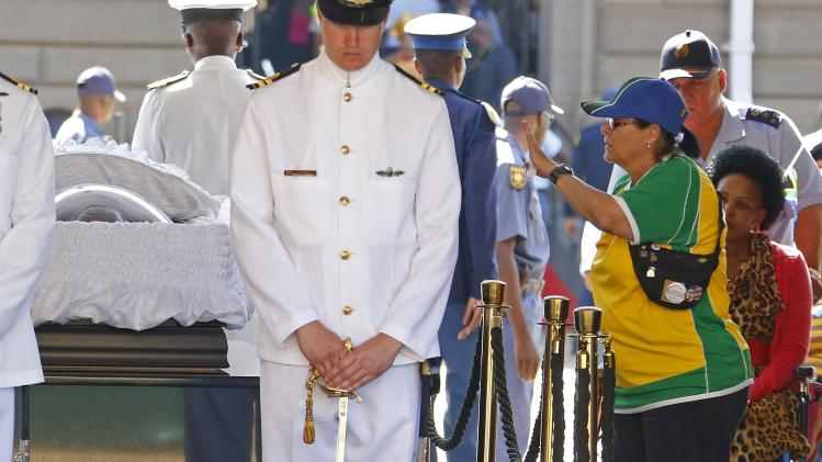A woman reacts while paying her respects at the coffin of former South African President Nelson Mandela, as Mandela lies in state at the Union Buildings in Pretoria