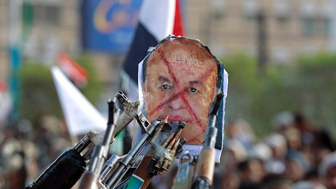 Followers of the Shiite Huthi rebel group aim their weapons at a defaced poster of  President Abedrabbo Mansour Hadi, during a demonstration against the air strikes by the Saudi-led coalition, in Yemeni capital Sanaa, on April 27, 2015