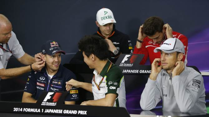A television crew member adjusts the microphone on Red Bull Formula One driver Vettel as he speaks to Caterham Formula One driver Kobayashi during a news conference at the Suzuka circuit in Suzuka
