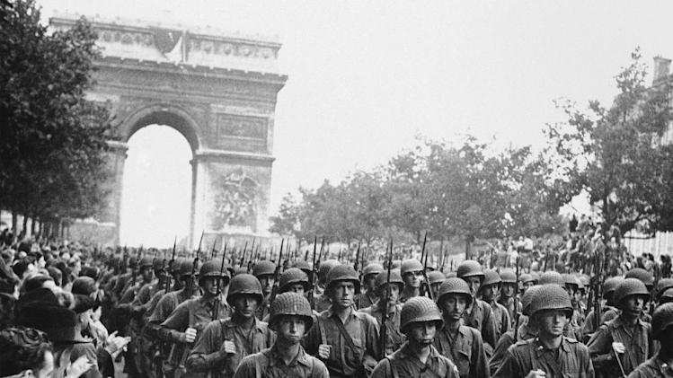 FILE-In this photo provided by the U.S. Office of War Information, American troops march down the Champs Elysees, past the Arc de Triomphe, Sept. 12, 1944, as residents of Paris throng the sidewalks to cheer following the liberation of Paris on August 25, 1944. (AP Photo/Richard Boyer, U.S. Office of War Information)