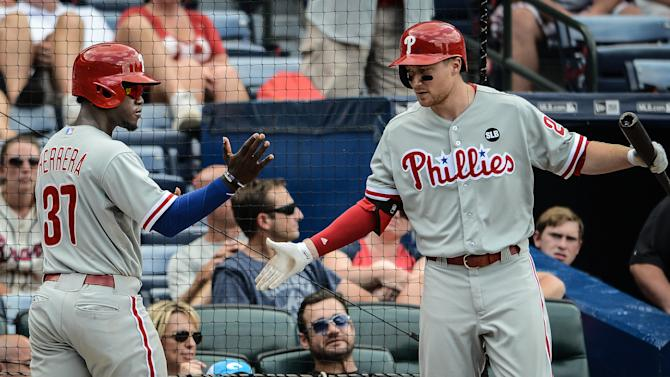 Philadelphia Phillies center fielder Odubel Herrera (37) is greeted by teammate Cody Asche (25) after scoring the go-ahead run on a sacrifice fly by first baseman Ryan Howard in the tenth inning of a baseball game against the Atlanta Braves Sunday, July 5, 2015, in Atlanta. (AP Photo/Jon Barash)