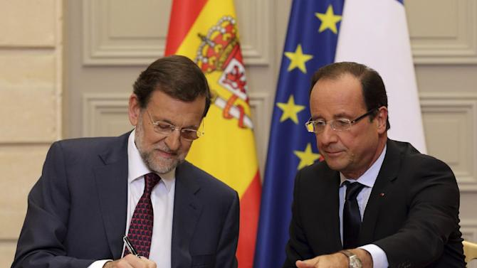 Spain's Prime Minister Mariano Rajoy, left, and French President Francois Hollande, sign cooperation agreements during a Franco-Spanish summit at the Elysee Palace, in Paris,  Wednesday, Oct. 10, 2012. (AP Photo/Philippe Wojazer, Pool)
