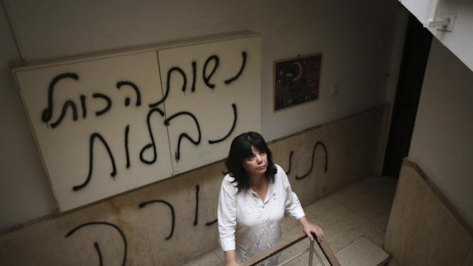 """Peggy Cidor, a leading member of the Women of the Wall organization, stands in the hallway of her building in Jerusalem, Monday, May 20, 2013. The group, known as """"Women of the Wall,"""" convenes monthly prayer services at the Western Wall, the holiest site where Jews can pray, wearing prayer shawls and performing rituals that ultra-Orthodox Jews believe only men are allowed to do. Israeli officials initially opposed the group but have recently backed its right to worship and earlier this month thousands of ultra-Orthodox protesters tried to prevent their prayer service. The graffiti in Hebrew reads, """"The women of the Western Wall are despised."""" (AP Photo/Michal Fattal) ***ISRAEL OUT***"""