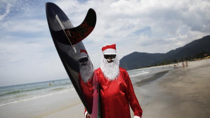 Carlos Bahia, dressed as Santa Claus, poses with his board at the Maresias beach, in the state of Sao Paulo