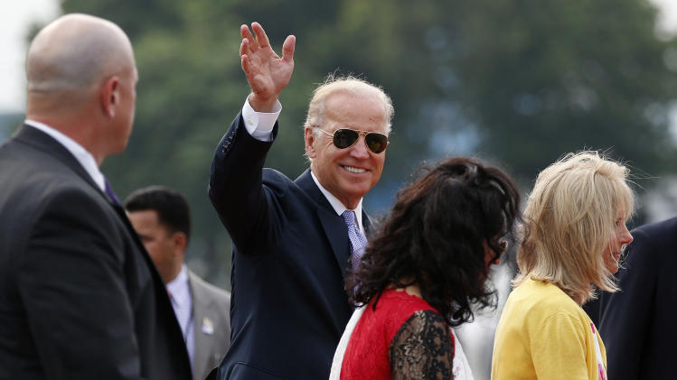 U.S. Vice President Joe Biden accompanied by his wife Jill, right, waves upon his arrival at the airport in New Delhi, India, Monday, July 22, 2013. Biden arrived in India Monday on a four day visit aimed at boosting trade and strengthening strategic relations as Washington pursues its new Asia-Pacific policy. (AP Photo/ Saurabh Das)