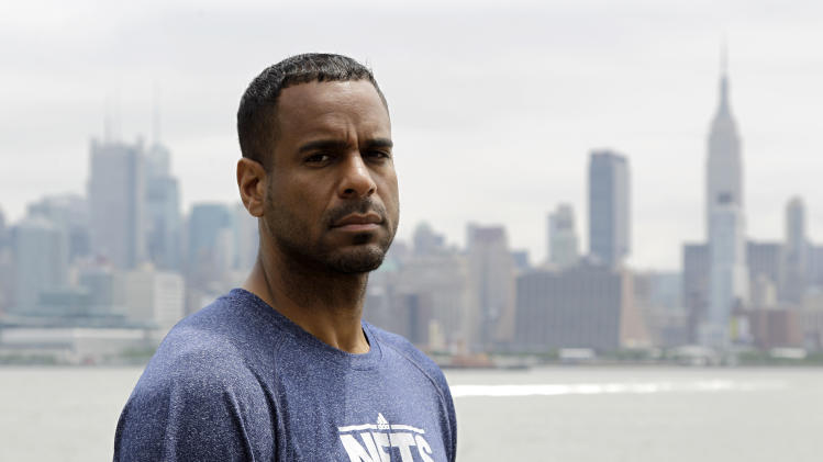 In this Tuesday, June 19, 2012, photo, former NBA basketball star Jayson Williams poses for The Associated Press near the Hudson River overlooking New York City in Weehawken, N.J. Williams, who was recently released from prison, is trying to plug himself back into society. (AP Photo/Julio Cortez)