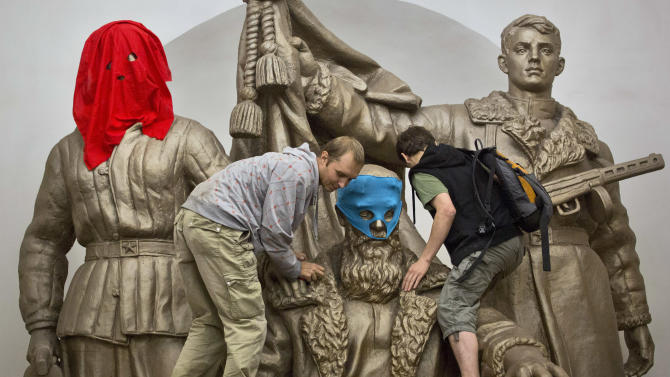 Pussy Riot punk group supporters place masks on a monument to WWII heroes to resemble Pussy Riot members, at an underground station in Moscow on Friday, Aug. 17, 2012. Three group members who were jailed in March following a guerrilla performance denouncing President Vladimir Putin in Moscow's main cathedral have unwillingly emerged as vivid — and very different — characters. They await a verdict Friday on charges of hooliganism motivated by religious hatred. (AP Photo/Yevgeny Feldman, Novaya Gazeta)
