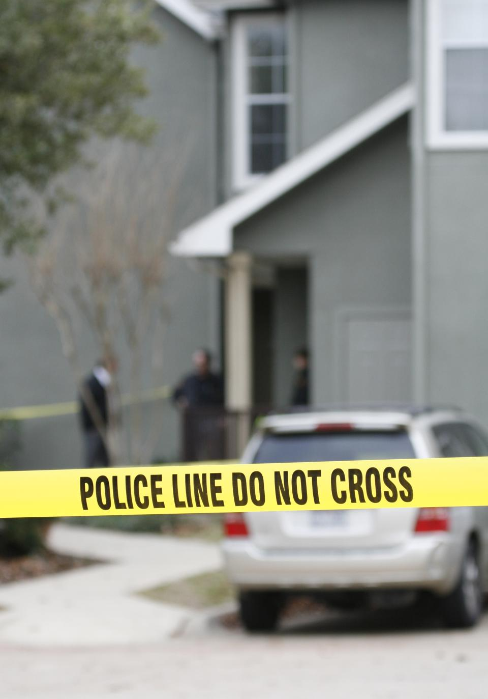 Police tape hangs in front of an apartment complex where 7 people were found dead, Sunday Dec. 25, 2010, in Grapevine, Texas. Four women and three men who police believe to be related were found apparently shot to death, and authorities said they believe the shooter is among the dead  (AP Photo/Mike Fuentes)