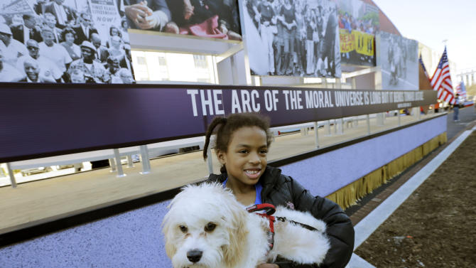 "Arianna Dorman of Fort Washington, Md., holds her dog ""Luke,"" as she poses for a picture with the civil rights movement float prepared for the 57th Presidential Inaugural Parade, Sunday, Jan. 20, 2013 in Washington. Thousands are planning to march in the 57th Presidential Inauguration parade after the ceremonial swearing-in of President Barack Obama on Monday. (AP Photo/Alex Brandon)"