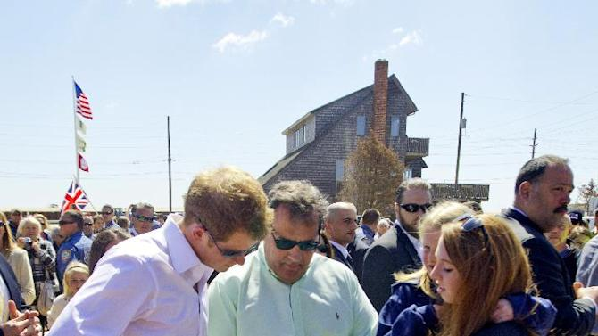 Britain's Prince Harry and N.J. Gov. Chris Christie look at a before photo of  a home that belongs to the Bowden family home which is now empty lot in Mantoloking, N.J. on Tuesday, May 14, 2013.  Prince Harry began a tour Tuesday of New Jersey's storm-damaged coastline, inspecting dune construction, walking past destroyed homes and shaking hands with police and other emergency workers.  (AP Photo/The Star-Ledger, Andrew Mills, Pool)