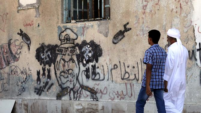 "In this Tuesday, Sept. 18, 2012 photo, Libyans walk by an anti-Moammar Gadhafi mural in Benghazi, Libya. The Arabic writing on the wall reads, "" the oppression regime."" In front of Benghazi's stock market, pedestrians step around lakes of sewage in the street. The grandest hotel in Libya's second largest city is a gloomy, state-owned bulk, with broken windows and dim corridors. Last week's deadly attack on the U.S. Consulate was just one sign of how the city is a tough customer: Benghazans are bitter over decades of neglect and humiliation under Moammar Gadhafi and they rumble with discontent that the new leadership in Tripoli still doesn't treat them as equals. (AP Photo/Mohammad Hannon)"