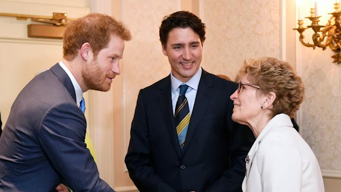 Prince Harry shakes hands with Ontario Premier Kathleen Wynne as Prime Minister Justin Trudeau looks on during the Prince's visit to Toronto