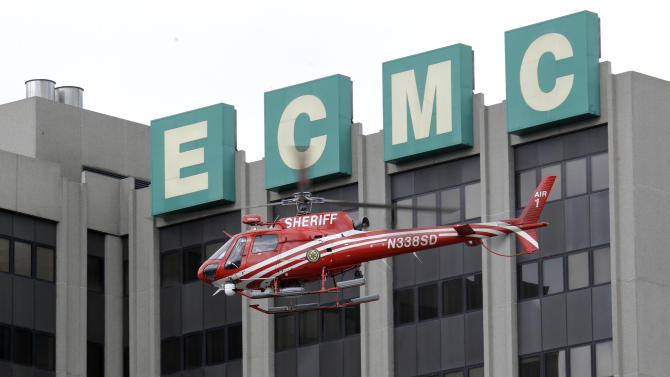"""An Erie County Sheriff's helicopter searches at the scene of a shooting at Erie Count Medical Center in Buffalo, N.Y., Wednesday, June 13, 2012.  A police official confirms that a woman was killed Wednesday morning on the grounds of the Erie County Medical Center, which he describes as being in """"complete lockdown"""" as SWAT teams and other officers cordon off the 65-acre campus. (AP Photo/David Duprey)"""