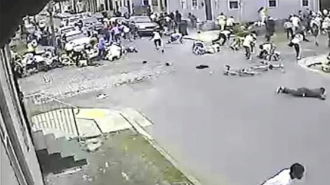 In this image taken from video and provided Monday, May 13, 2013, by the New Orleans Police Department, a possible shooting suspect in a white shirt, bottom center, shoots into a crowd of people, Sunday in New Orleans. Police believe more than one gun was fired in the Mother's Day gunfire that wounded 19 people during a New Orleans neighborhood parade. (AP Photo/New Orleans Police Department)