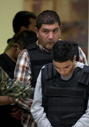 """The alleged leader of a faction of the hyper-violent Zetas cartel, Ivan Velazquez Caballero, known as """"El Taliban,""""  is escorted to a media presentation at the Mexican Navy's Center for Advanced Naval Studies in Mexico City,Thursday, Sept. 27, 2012. Velazquez Caballero allegedly has been fighting a bloody internal battle with top Zetas' leader Miguel Angel Trevino Morales, and officials have said the split was behind a recent surge in massacres and shootouts, particularly in northern Mexico. (AP Photo/Eduardo Verdugo)"""