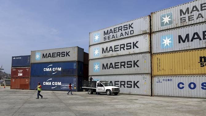 Port workers walk by a container area at the port in La Guaira