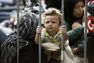 A child sits with other refugees behind a fence  between…