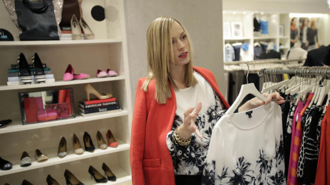 "In this Wednesday, Jan. 23, 2013 photo, creative director for Ann Taylor, Lisa Axelson discusses fashion at Ann Taylor's renovated location in The Westchester shopping mall in White Plains, N.Y. She pointed out the styles that she believes are the cornerstone of a woman's wardrobe in 2013. The store is set up like a closet, without a specific ""suits section"" or all the denim tucked in the back corner.   (AP Photo/Seth Wenig)"