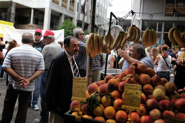 A street vegetable vendor discusses Greece&#39;s crisis with a man as in the background is seen a protest outside the ministry of Finance, in central Athens, on Wednesday, Sept. 12, 2012. A fresh wave of anti-austerity strikes hit Greece Wednesday as the leaders of the governing coalition struggled to finalize further spending cuts for the coming two years  without which the country will lose its vital rescue loans.(AP Photo/Petros Giannakouris)