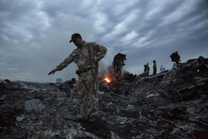People walk amongst the debris at the crash site of …