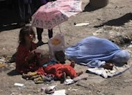 An Afghan woman with her children begs for money on June 13 in Jalalabad, Nankarhar province. Science academies have emphasized the need to help millions rise out of poverty, brake trends of reckless consumption and address population growth