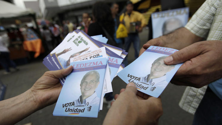 A man distributes campaign fliers promoting Caracas Metropolitan Mayor Antonio Ledezma, who is running for re-election, on a street in Caracas, Venezuela, Thursday, Dec. 5, 2013. Venezuelans will vote in nationwide municipal elections Sunday. (AP Photo/Ariana Cubillos)