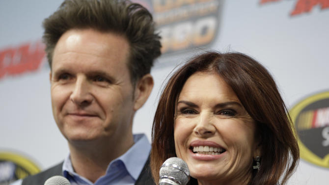 Mark Burnett, left, and Roma Downey talk to the media prior to the start of the STP 500 Sprint Cup series auto race at Martinsville Speedway in Martinsville, Va., Sunday, April 7, 2013.  Downey is the grand marshal for Sunday's race.  (AP Photo/Steve Helber)