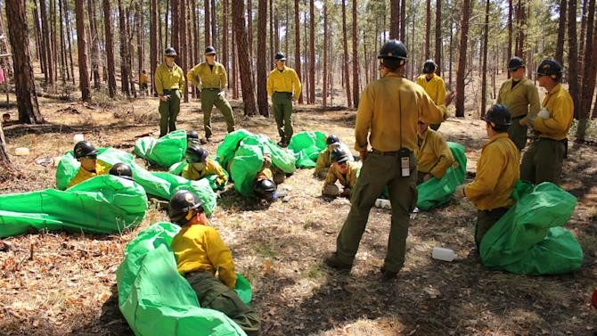In this April 12, 2012 photo provided by the Cronkite News, Phillip Maldonado, a squad leader with the Granite Mountain Hotshots, trains crew members on setting up emergency fire shelters outside of Prescott, Ariz. On Sunday, June 30, 2013, 19 members of the Prescott-based crew were killed in the deadliest wildfire involving firefighters in the U.S. for at least 30 years. The firefighters were forced to deploy their emergency fire shelters - tent-like structures meant to shield firefighters from flames and heat - when they were caught near the central Arizona town of Yarnell, according to a state forestry spokesman. (AP Photo/Cronkite News, Connor Radnovich)