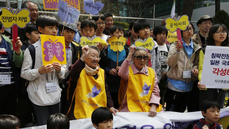 "FILE - In this April 24, 2013 file photo, South Koreans, Kim Bok-dong, center right, and Gil Wen-oak, center left, who were forced to serve for the Japanese Army as sexual slaves, so called ""comfort women,"" during World War II, shout slogan with their supporters in an anti-Japan protest against the Japanese lawmakers' visit to the Yasukuni Shrine, in front of the Japanese Embassy in Seoul, South Korea. More than 70 years ago, at age 14, Kim Bok-dong was ordered to work by Korea's Japanese occupiers. She was told she was going to a military uniform factory, but ended up at a Japanese-military-run brothel in southern China. (AP Photo/Kin Cheung, File)"