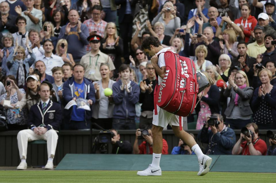 Roger Federer of Switzerland walks off the court after his defeat to Sergiy Stakhovsky of Ukraine in their Men's second round singles match at the All England Lawn Tennis Championships in Wimbledon, London, Wednesday, June 26, 2013. (AP Photo/Alastair Grant)