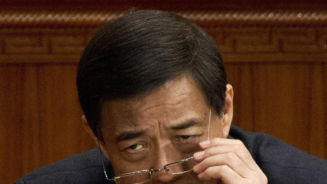 FILE - In this Sunday, March 11, 2012 file photo, then Chongqing party secretary Bo Xilai adjusts his glasses during a plenary session of the National People's Congress at the Great Hall of the People in Beijing.  Chinese lawmakers stripped disgraced politician Bo Xilai of his last official position Friday, Oct. 26m, 2012, formally expelling him from the country's top legislature and setting the stage for criminal proceedings against the once-rising political star. Though largely a formality since Bo was purged from the Communist Party late last month, his expulsion from the congress removes his immunity from prosecution. That sets the stage for a criminal case involving accusations of corruption and abuse of power.   (AP Photo/Andy Wong, File)
