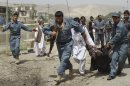 Afghan policemen evacuate a wounded person after a suicide bomber struck outside a provincial council headquarters in Pul-i-Khumri, Baghlan province, northern Afghanistan, Monday, May 20, 2013, killing the council chief and at least more than a dozen others, authorities said. Afghan President Hamid Karzai condemned the bombing saying the killing of civilians shows the true nature of the Taliban, who seek to re-establish the strict interpretation of Islamic law they imposed for five years before being ousted in the 2001 U.S.-led invasion over its sheltering of al-Qaidas terrorist leadership. (AP Photo/Jawed Basharat)