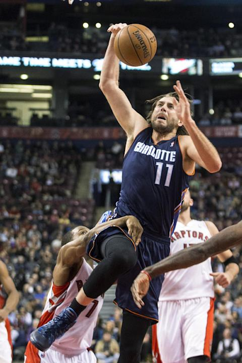 Charlotte Bobcats' Josh McRoberts scores on Toronto Raptors' Kyle Lowry during the first half of an NBA basketball game in Toronto on Wednesday, Dec. 18, 2013