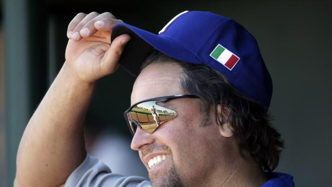 """FILE - In this March 6, 2013 file photo, Italy hitting coach and former Major League Baseball catcher Mike Piazza adjusts his hat during an exhibition spring training baseball game against the Los Angeles Angels in Tempe, Ariz. Piazza will be taking center stage with the Miami City Ballet. The Miami Beach-based dance company has tapped Piazza to play the role of a gangster in the May 3 production of """"Slaughter on Tenth Avenue."""" (AP Photo/Morry Gash, File)"""