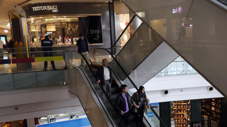 People ride an escalator inside a shopping mall in Buenos Aires