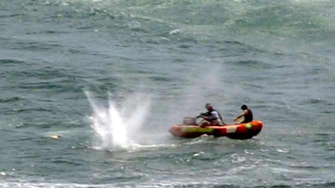 "Police in inflatable rubber boats shoot at a shark off Muriwai Beach near Auckland, New Zealand, Wednesday, Feb. 27, 2013, as they attempt to retrieve a body following a fatal shark attack. Police said a man was found dead in the water after being ""bitten by a large shark."" (AP Photo/Ross Land) NEW ZEALAND OUT, NO SALES"