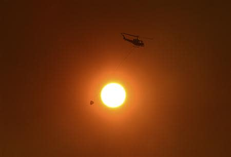 Helicopter with bucket used for carrying water for dropping onto bushfires, flies past the sun as it is obscured by smoke in western Sydney