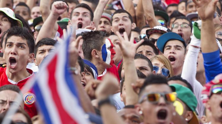 Costa Rica soccer fans celebrate a goal against Greece as they watch the World Cup round of 16 match on TV set up in a public square in San Jose, Costa Rica, Sunday, June 29, 2014