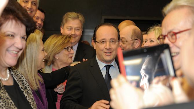 French President Francois Hollande, center, is welcomed by members the socialist group at the European Parliament, Tuesday Feb 5, 2013, in Strasbourg, eastern France. Hollande warns of a tough European Union summit later this week if countries including Britain continue to demand drastic cuts to the EU budget while refusing to make concessions themselves.  (AP Photo/Christian Lutz, POOL)