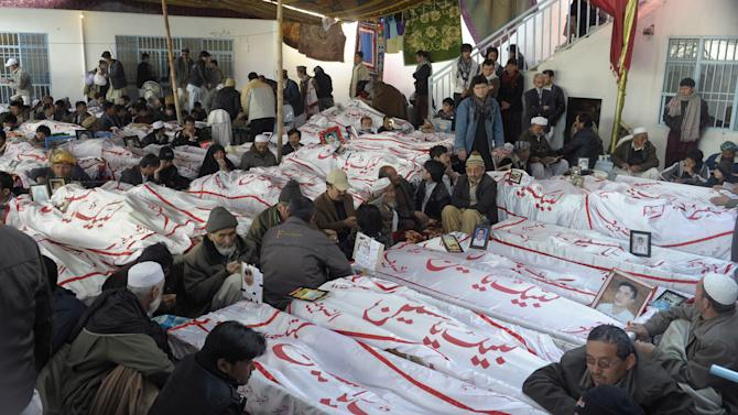 Pakistani Shiite Muslims mourn next to the bodies of their relatives, a victims of Saturday's bombing that killed scores of people, as relatives refuse to bury their dead in protest, in Quetta, Pakistan, Tuesday, Feb. 19, 2013. Pakistan on Tuesday ordered a security operation in response to the weekend bombing targeting minority Shiites that killed 89 people in the southwestern city of Quetta and sacked the top police officer in the surrounding Baluchistan province. (AP Photo/Arshad Butt)