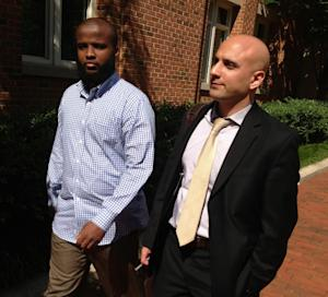 """Gulet Mohamed, 21, left, leaves the federal court in Alexandria, Va., Friday, Aug. 16, 2013, with his attorney, Gadeir Abbas, with the Council on American-Islamic Relations, after a hearing challenging his placement on the government's no fly list. Mohamed sued more than two years ago after getting stuck in Kuwait, and recently had his lawsuit reinstated by the 4th U.S. Circuit Court of Appeals in Richmond."""" (AP Photo/Matthew Barakat)"""