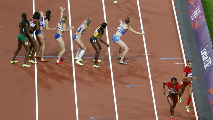 United States' Deedee Trotter and United States' Allyson Felix do a handoff to take the lead in the women's 4 x 400-meter relay during the athletics in the Olympic Stadium at the 2012 Summer Olympics, London, Saturday, Aug. 11, 2012. (AP Photo/Daniel Ochoa De Olza)