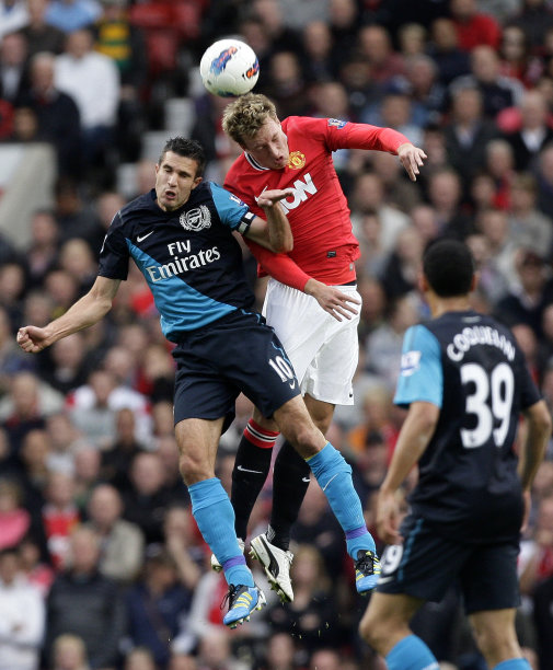 Manchester United's Phil Jones, center, vies for ball against Arsenal's Robin van Persie during their English Premier League soccer match at Old Trafford, Manchester, England, Sunday Aug. 28, 2011. (AP Photo/Jon Super)