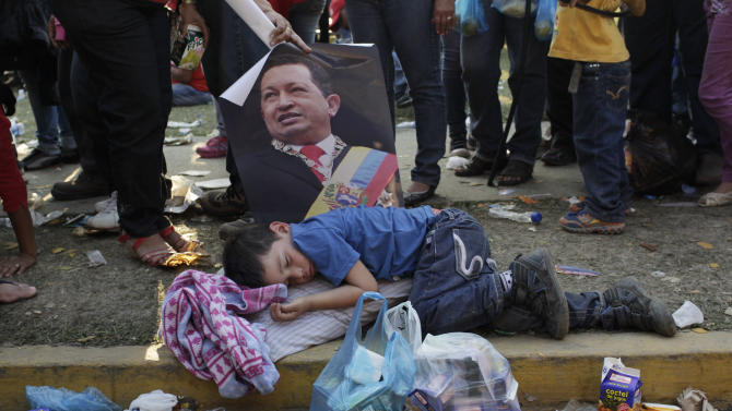 A woman holds a poster of Venezuela's late President Hugo Chavez over a sleeping boy as she stands in line to see Chavez's body lying in state at the military academy in Caracas, Venezuela, Friday, March 8, 2013. Chavez died on March 5 after a nearly two-year bout with cancer.  He was 58. The line to see Chavez's body stretched 1½ miles (2 kilometers) but was halted as his state funeral got under way. (AP Photo/Rodrigo Abd)