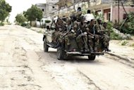 A Somali military vehicle transports troops to a frontline in the Wardhigley district, in restive Mogadishu. Somali government forces and African Union troops battled insurgents on Thursday in heavy fighting in the capital Mogadishu in efforts to secure aid routes for drought victims