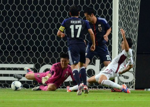 Venezuela's forward Nicolas Fedor (R) scores past Japanese goalie Eiji Kawashima (L)